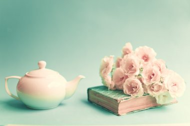 White roses over a vintage book and white teapot stock vector
