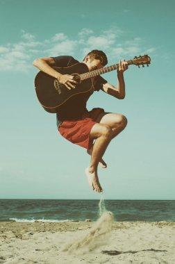 Boy playing guitar on the beach