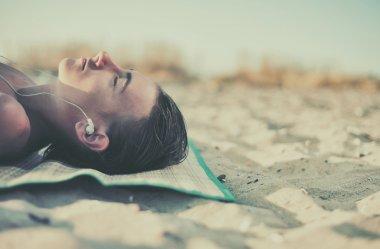 Boy listening music at headphones on beach