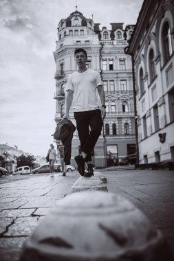 Guy stand on the city street, look camera and around