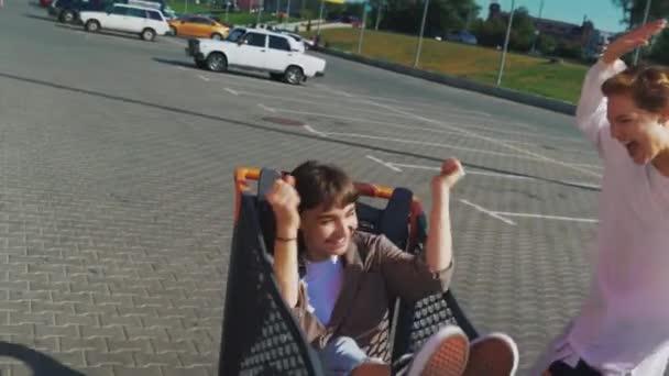 Přítelkyně jezdit ve vozíku v supermarketu na ulicích města.