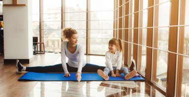Mother and daughter makeing yoga in the gym