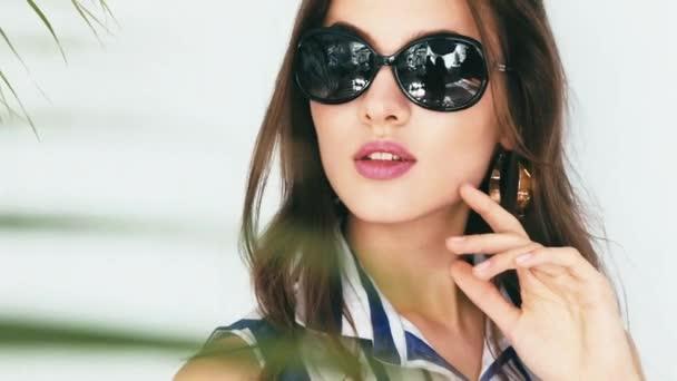Szép szexi barna női napszemüvegek nyári kollekció elegáns finom ujjak manikűr kéz leveszi a szemüvegét, és keres el ruhák divat üzletasszony palm hagy árnyék