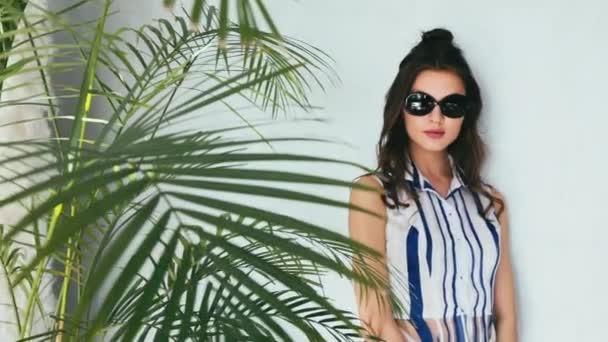 Sexy kráska žena hedvábné šaty luxusní elegantní móda sluneční brýle značky rukou vak módní šperky styl pro strana datum glamour pozice letní palm oblečení kolekce bruneta vlasy taneční modelu make-up příslušenství