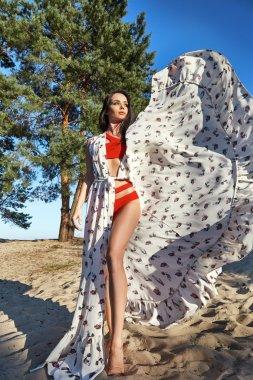 Sexy beautiful woman tanned perfect body silk dress beach sand