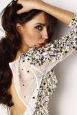 Porträt von schönen sexy Frau mit schönen Make-up in einem brillanten Abendkleid aus Seide oder Chiffon mit Edelsteinen bestickt