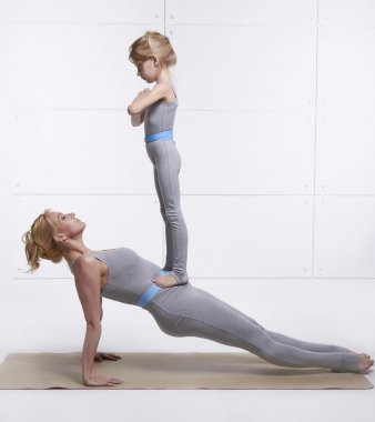 Mother and daughter doing yoga exercise, fitness, gym wearing the same comfortable tracksuits family sports, sports paired woman put her hands on the floor child standing on her abdomen girl balancing
