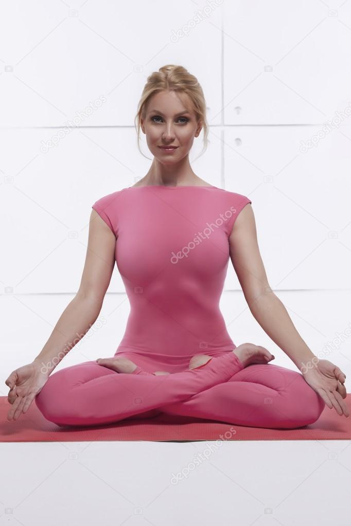 Beautiful sexy blonde with perfect athletic slim figure engaged in yoga, exercise or fitness, lead a healthy lifestyle, and eats right, dressed in comfortable casual clothes relaxes and meditation