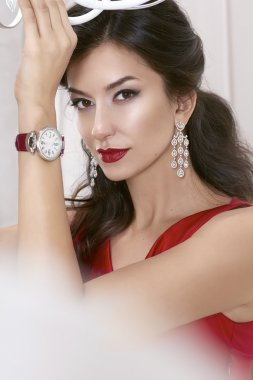 Beautiful sexy woman brunette Brown eyes in a red dress in lavish earrings with diamonds and watches on the Burgundy leather strap evening makeup, red lipstick, raised a hand up