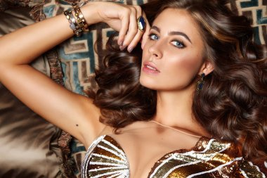 Beautiful sexy brunette woman with wavy hair in a bright multi-colored suit on the wide shoulder straps with rings bracelets accessories, or evening hairstyle and makeup sitting in chair with cushions
