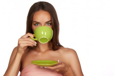Young beautiful sexy girl with dark hair, bare shoulders and neck, holding big green cup of coffee or tea to enjoy the taste and are dieting, healthy drinking, feeling temptation and relaxation