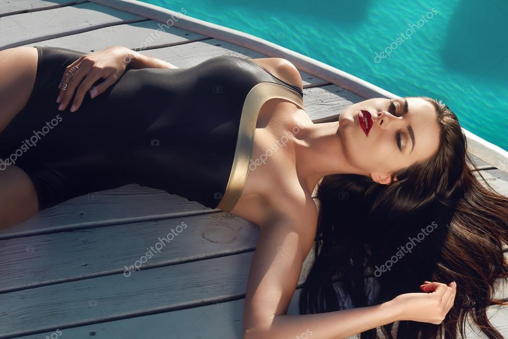 Sexy woman is sunning by swimming pool have fun at beach ...