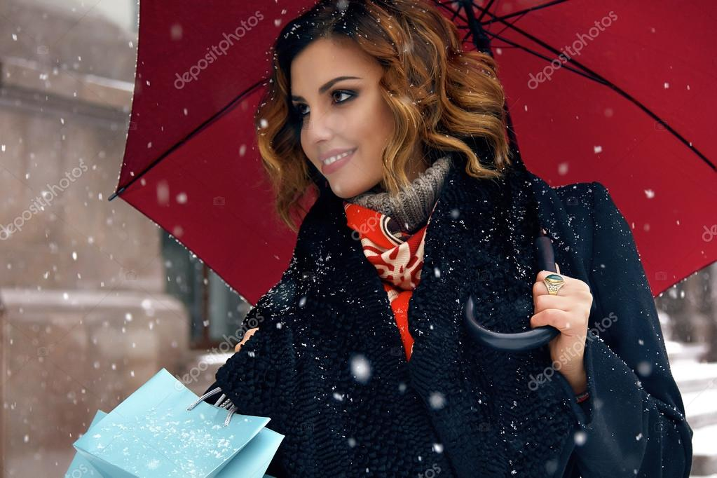 Beautiful woman snow street buy presents Christmas New Year