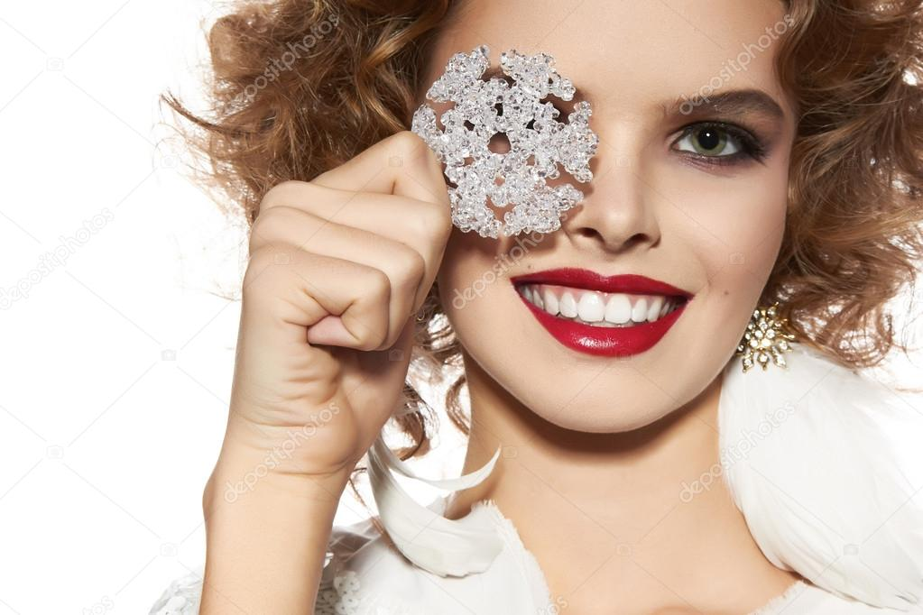 Beautiful girl with evening makeup smile take cristal snowflake