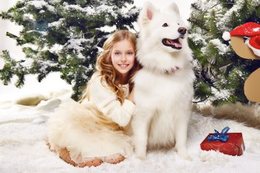 Beautiful little girl sitting in the snow at Christmas trees