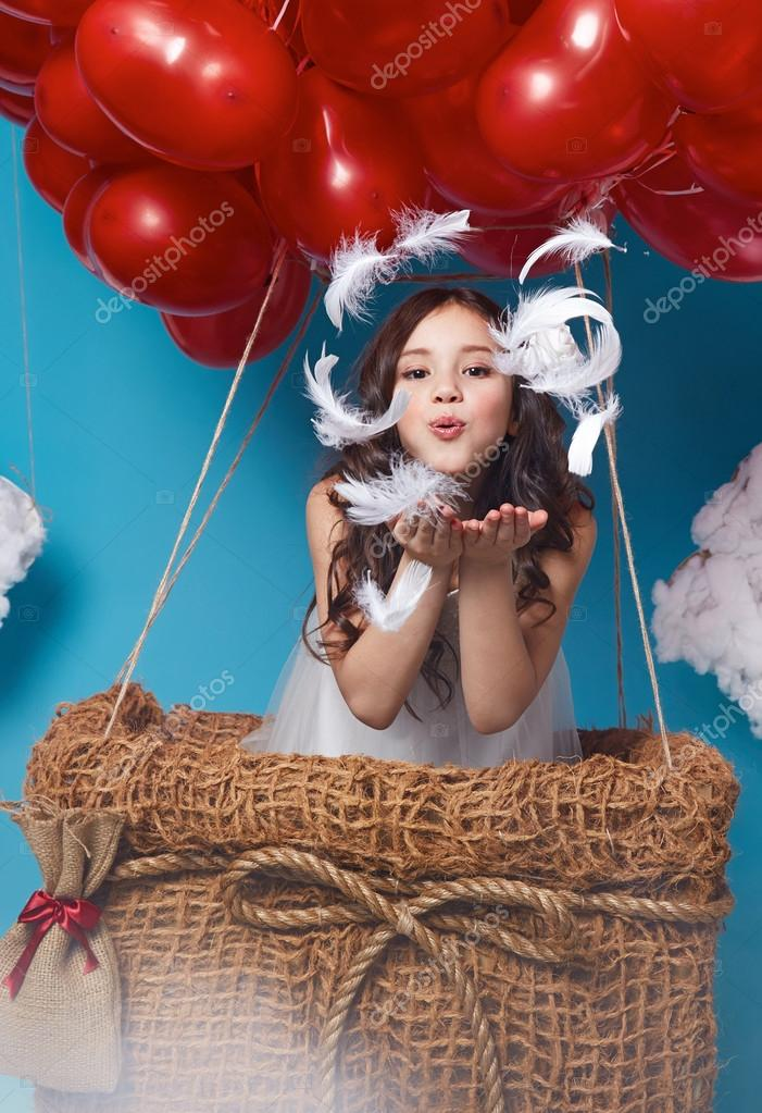 Small cute girl flying on red heart balloons Valentines day