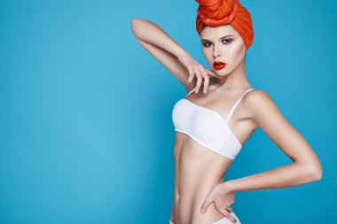 Beautiful young sexy girl with bright makeup perfect slim figure trained body and tan diet fitness club wearing a white stylish trendy top and orange headscarf sport underwear
