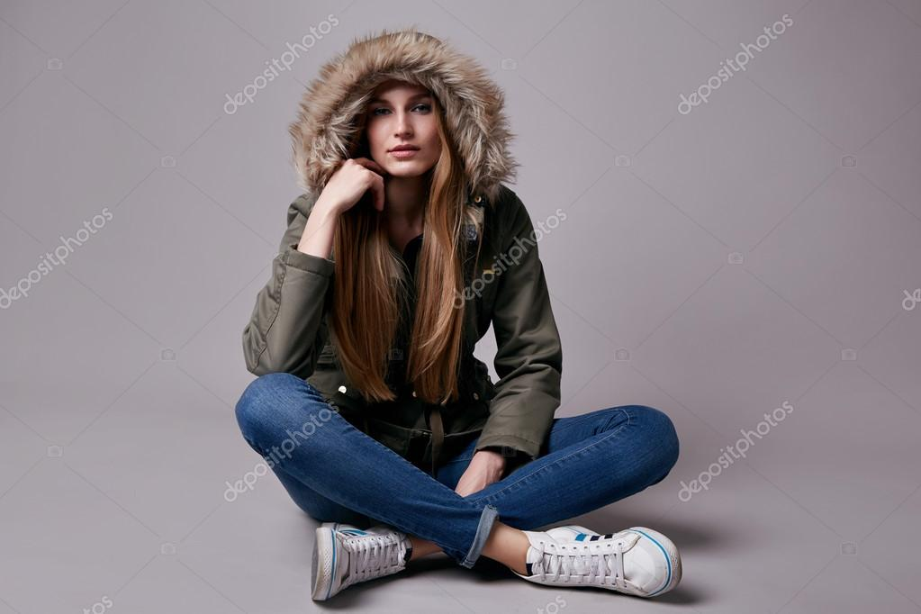 Beautiful young teen girl with long blonde hair with natural make-up  wearing jeans and jacket park and sneakers on the floor model with a clothing  catalog ...