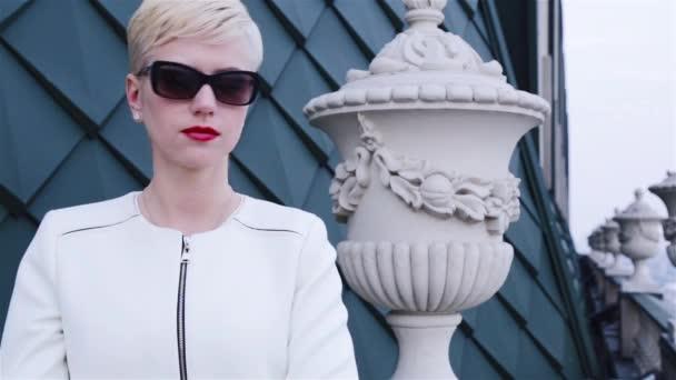 Beautiful sexy blond business women wearing sunglasses white jacket waiting meeting speak phone city streets