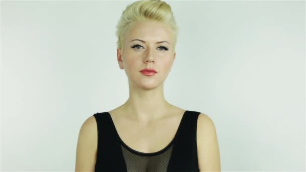 Beautiful young blonde girl with short hair wearing a black dress with bare shoulders smiling expresses emotions joy sexy tenderness