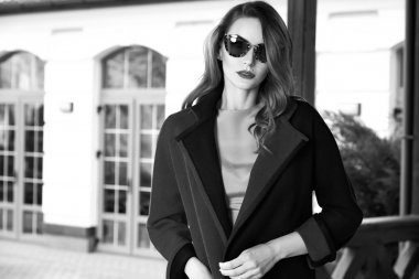Beautiful fashionable young business woman wearing in ?rimson autumn coat and sunglasses with hairdo and makeup walking on a street with fall near big house and trees without yellow leaves background