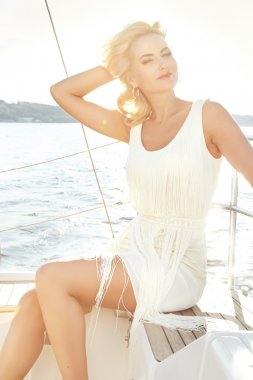 Beautiful young sexy blond woman in a dress and makeup, summer trip on a yacht with white sails on the sea or ocean in the Gulf marine of the wind and the breeze in the sun tans romantic