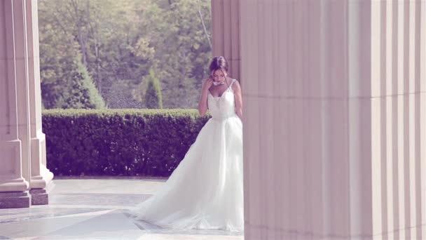 Gyönyörű fiatal nő szexi barna menyasszony egy luxus fehér esküvői ruha a természet kastély nyári boldogság vár a vőlegény az esküvő előtt