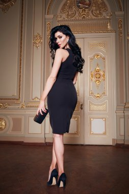 Beautiful sexy woman in elegant dress fashionable autumn Collection of spring long brunette hair makeup tanned slim body figure accessories interior luxury castle gold monogram baroque palace of Queen
