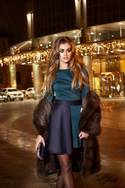 Beautiful young sexy blonde wearing evening makeup in elegant fitting dress fashionable stylish expensive fur coat walk night street lights evening hand  handbag luxury rich life going party concert