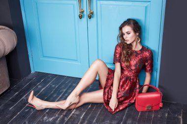 Beautiful young sexy woman in smart evening dress red silk dress new stylish fashion collection autumn winter season, long brown hair, shoes, interior blue door in the bedroom room.