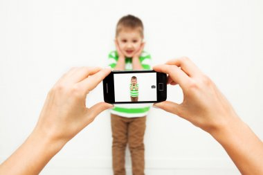 Young woman taking picture of her son with smartphone.