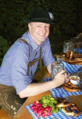Man in bavarian costume sitting in a beergarden stock vector