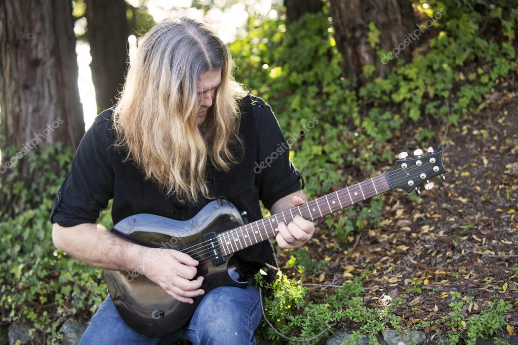 man playing guitar in a park
