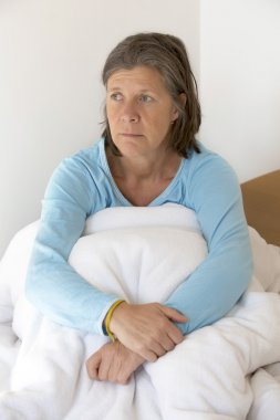 sad woman sitting in bed