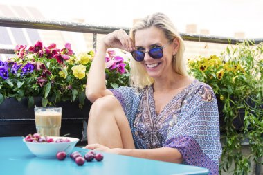 blond woman sitting on balcony with coffee and cherries