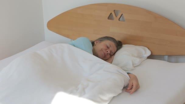 Frau in ihren 50ern mit Kopfschmerzen aufwachen