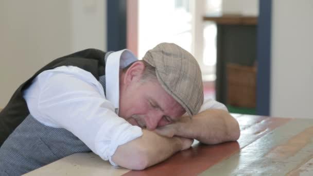 muž spí u stolu a probudil s bolestí hlavy