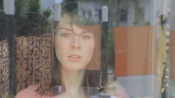 mladá žena čištění vypadá otráveně oknem na kameru a okna