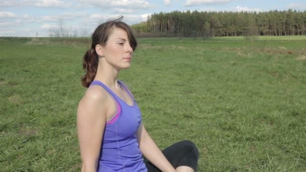 giovane donna in sport gear seduti allaperto in erba ed è meditando