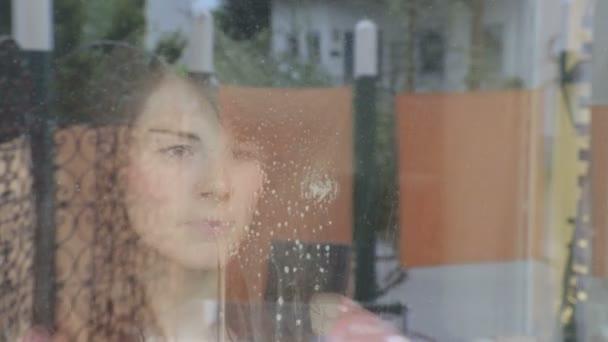 mladá žena, čištění, usmívá se oknem na kameru a okna