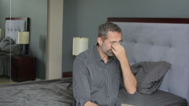 Man in shirt sitting on a bed and looking distressed