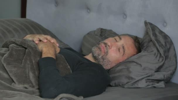 muž ležel v posteli a spí