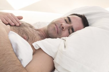 shirtless man sleeping in bed
