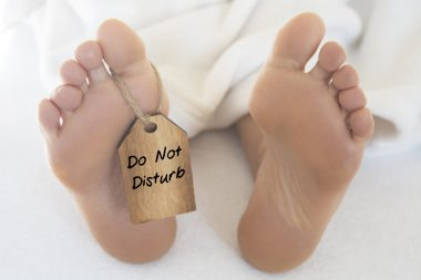 naked feet  with wooden tag 'do not disturb