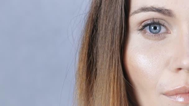 Krásná žena polovinu tváře portrét ve studiu na šedém pozadí