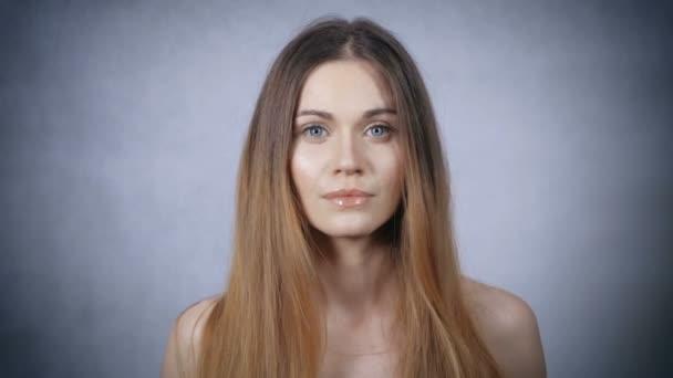 portrét krásné blond ženy na šedém pozadí.