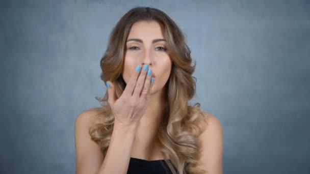 Mladá krásná žena vzduchem pusu posílá šedé pozadí