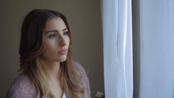 Strach, krásná mladá žena při pohledu z okna