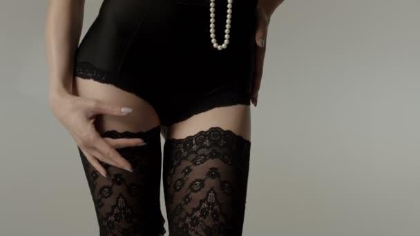 Řez portrét ženské tělo nosí černé spodní prádlo a dlouhé perly.