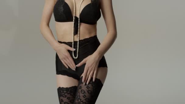 Vágott fekvő női test viselt fekete fehérnemű és hosszú gyöngy.